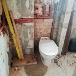 A fürdő másik oldala szélesebb, hogy elférjen az elfalazott cső előtt a mosdó, mellette meg a vécé és a bojler